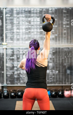 Rear view of a muscular young woman swinging a kettlebell weight and holding it above her head with one hand during training inside a gym - Stock Photo