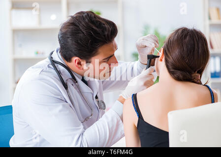 Doctor checking patients ear during medical examination - Stock Photo
