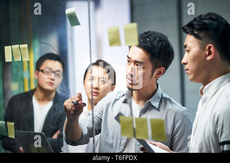 young asian entrepreneur of small company drawing a diagram on glass during team workshop in office discussing and formulating business strategies. - Stock Photo