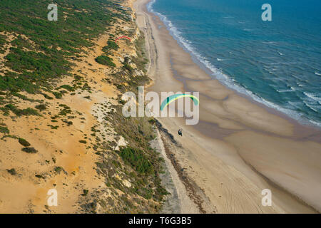 PARAGLIGER USING A FAIRLY STRONG SEA BREEZE TO SOAR ALONGSIDE A SCENIC CLIFF (aerial view). Matalascañas, Andalusia, Spain. - Stock Photo