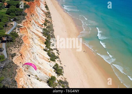 PARAGLIDER USING THE SEA BREEZE TO SOAR ALONGSIDE A COLORFUL SEASIDE CLIFF (aerial view). Praia da Falésia, Albufeira, Algarve, Portugal. - Stock Photo