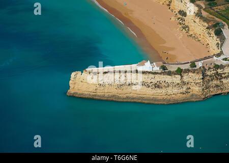 SMALL CHAPEL ON A HIGH AND NARROW PENINSULA (aerial view). Fort of Nossa Senhora da Rocha, Lagoa, Algarve, Portugal. - Stock Photo
