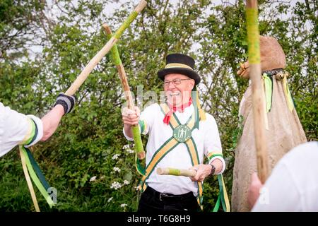 Wilmington, UK. 1st May, 2019.  Longman Morris dancing in the misty dawn beneath the Long Man of Wilmington on the South Downs, forming part of their May Day celebrations near Eastbourne, East Sussex. Credit: Jim Holden/Alamy Live News - Stock Photo