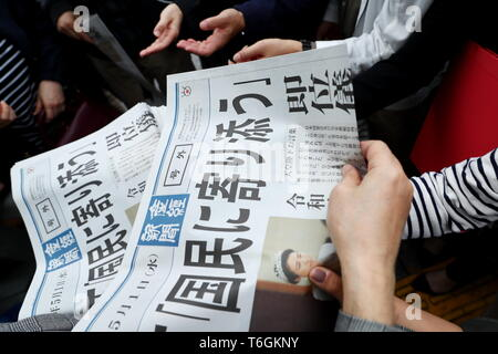 People try to receive a copy of extra edition of a newspaper reporting new emperor Naruhito's ascension on the front page in Tokyo's Ginza shopping district, Japan on May 1, 2019, the first day of the Reiwa Era. Credit: Naoki Nishimura/AFLO/Alamy Live News - Stock Photo