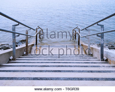 concrete stairs leading into water - Stock Photo