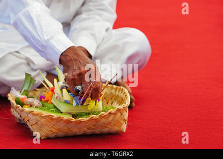 In hindu temple priest mangku praying and making offerings ritual before traditional Balinese New Year and silence day Nyepi. Holidays, festivals, art - Stock Photo