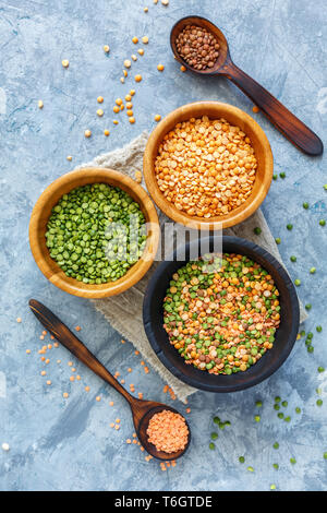 Lentils, green and yellow peas in bowls. - Stock Photo