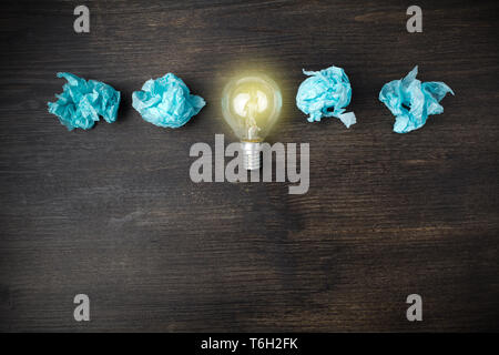 great idea concept with crumpled light blue paper and light bulb on wooden background - Stock Photo