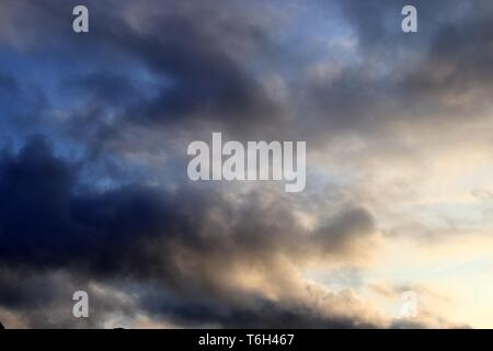 Beautiful mixed cloud formation with white and grey cumulus clouds in the sunlight - Stock Photo