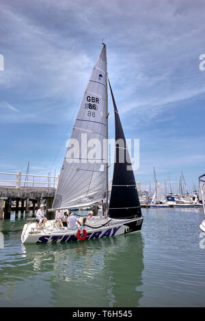 Group of friends heading off for a sailing trip in their small yacht - Stock Photo