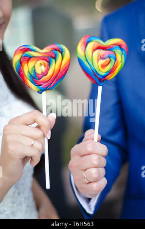 Sweet colorful candy hearts on sticks in the hands of the bride and groom - Stock Photo