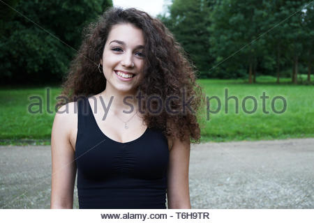 beautiful young woman with brunette long curly hair in nature - Stock Photo