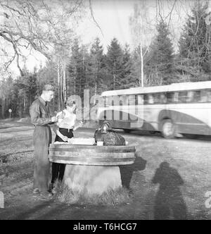 Lifestyle in the 1950s. A young couple has stopped to have a coffee and a sandwich by the roadside. An old millstone makes a good table for the picnic. Photo Kristoffersson Ref BF76-7. Sweden 1952 - Stock Photo