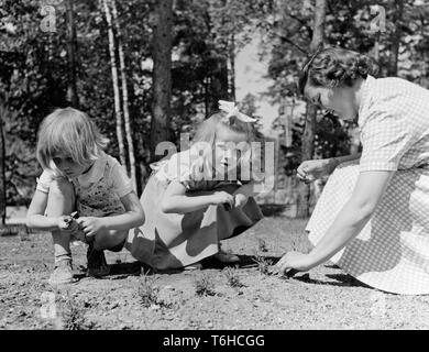 1950s day care. Two children and a woman is playing outdoors at a nursery school. Sweden 1953 - Stock Photo