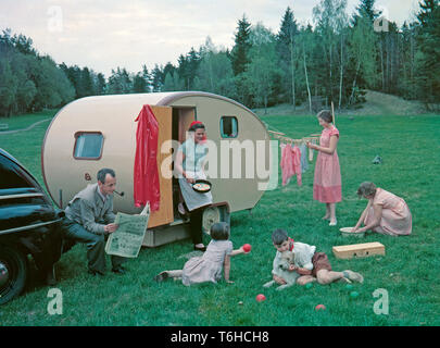 1950s camping. A family is enjoying their holiday and the practial camping life in their caravan. Demonstrating how well everything works for them even on holiday. The mother has fried some eggs and and steps out of the caravan holding the pan. Her eldest daughters are washing dishes and hanging up the laundry to dry. The youngest children are playing and the father of course sits around doing nothing more then having a smoke and reading the newspaper as a typical 1950s father would do.Everything in this pictures illustrates very well the time of the 1950s both in visible objects and clothing. - Stock Photo