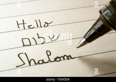 Beginner Hebrew language learner writing Hello Shalom word in Hebrew alphabet on a notebook close-up shot - Stock Photo