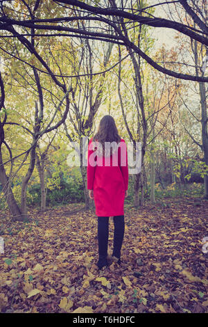Woman all alone in the forest with a long red coat, facing away - Stock Photo