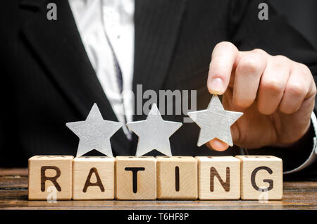 Businessman puts the third star above the word Rating on wooden blocks. The concept of quality of service. Hotel or restaurant rating. Evaluation of c - Stock Photo