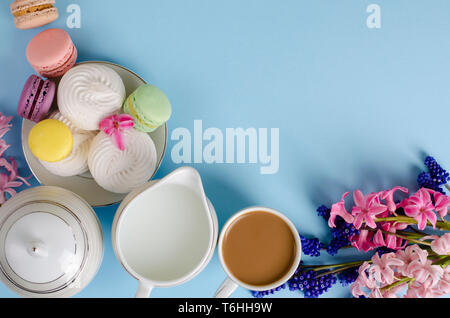 Cup of coffee with milk, white meringues, macarons, milk jar on pastel blue background decorated with muscari and hyacinth flowers. Top view, flat lay - Stock Photo