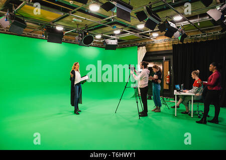 A wide-angle shot of a multi-ethnic group of people working in a film studio, a mature caucasian woman can be seen presenting in front of a green scre - Stock Photo