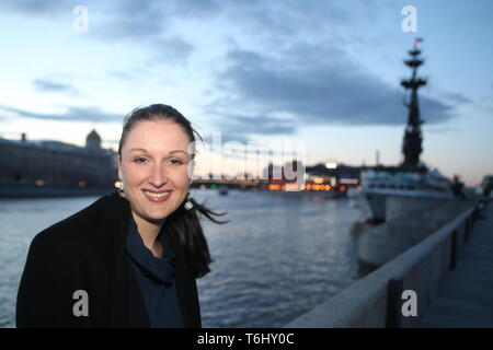 Young Russian woman smiling enjoys fresh summer breeze from the river on June evening in Moscow by Moscow river near Peter  Great historical monument. - Stock Photo