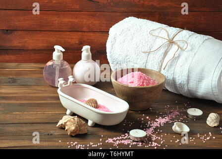 Spa and body care products. Aromatic rose bath Dead Sea Salt on the dark wooden background. Natural ingredients for homemade body salt scrub. - Stock Photo