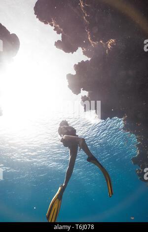 Asian girl freediving in famous Bells, Egypt - Stock Photo