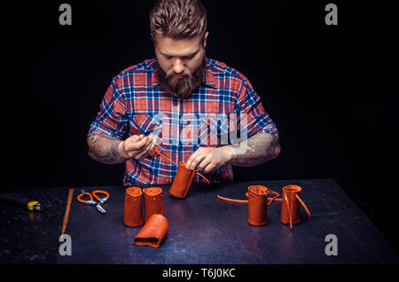 Artisan cutting leather outlines for his new production in his leather studio - Stock Photo