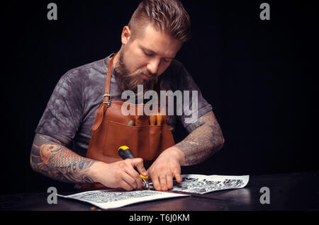 Handyman focusing on his work at his tanning shop - Stock Photo