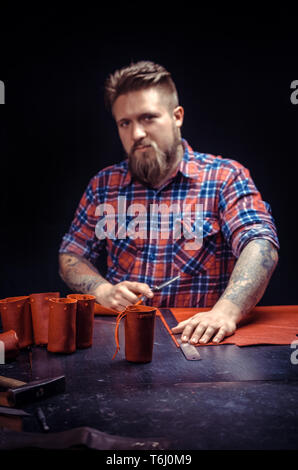 Craftsman creating a new leather product at his workshop - Stock Photo