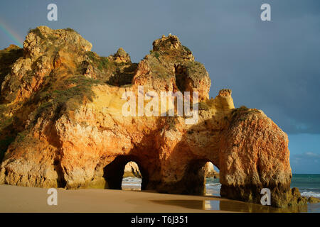 DOUBLE SEA ARCH AFTER A RAINSTORM, LIGHT RAINBOW IN THE UPPER LEFT. Near Prainha Beach, Alvor, Algarve, Portugal. - Stock Photo