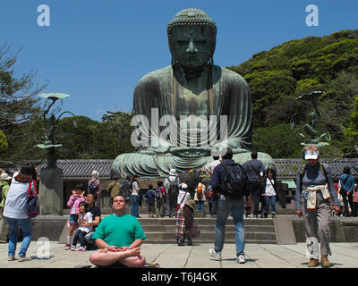 Turist meditating in lotus position under The Great Buddha (Daibutsu) on the grounds of Kotokuin Temple in Kamakura, Japan. - Stock Photo