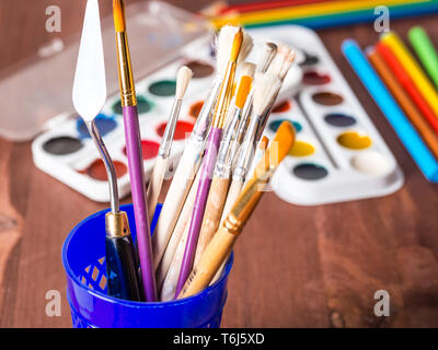 Artistic brushes in a cup closeup on a blurred background - Stock Photo