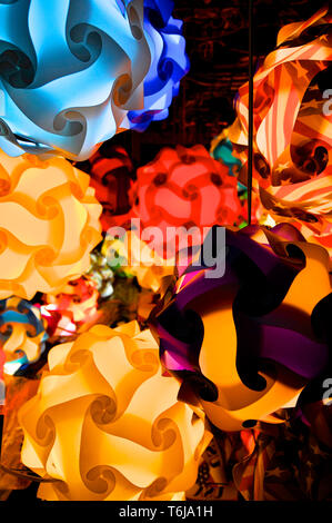 Close up picture of many colored puzzle lamps hanging from the ceiling of a shop in Quincy Market in Boston - Stock Photo