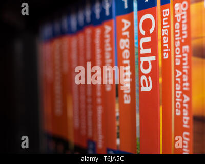 Chieti, Italy - April 4, 2019: Books of the Lonely Planet series on the bookcase with only the book of Cuba in focus, with nobody - Stock Photo