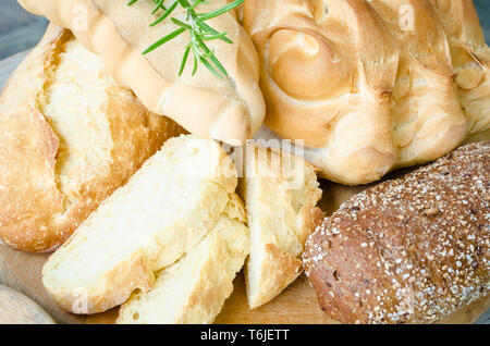 Assortment of freshly baked crusty loaves of bread and buns with ears on wooden table background. Rustic vintage style. Top view. - Stock Photo