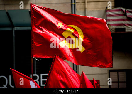 Communist flags as workers march during  May Day rally in the center of Barcelona. - Stock Photo