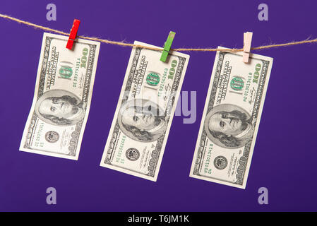 One hundred dollars hanging on clothesline with wooden clips on blue background. - Stock Photo