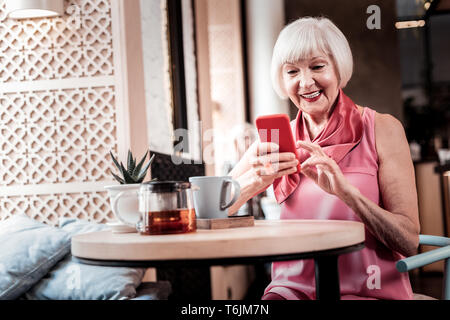 Cheerful old lady comfortably sitting in a cafe - Stock Photo