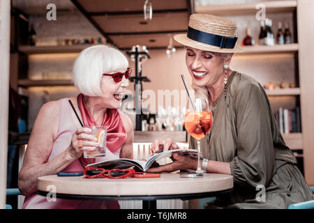 Laughing good-looking senior girlfriends sitting together in a cafe - Stock Photo