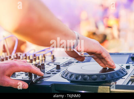 Dj mixing at beach party festival with people dancing in the background - Deejay playing music mixer audio outdoor - Concept of summer events - Stock Photo