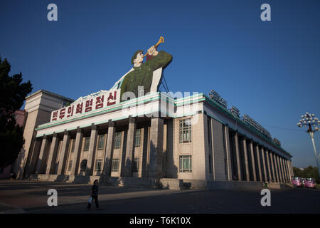 A building on the corner of Kim Il Sung Square in Pyongyang has a large image of a bugler with messages on the roof. - Stock Photo