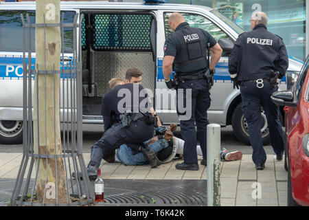 Wolfsburg, Germany, May 1, 2019: A dark-skinned man is handcuffed by German police officers in black uniforms and held at the bottom of the sidewalk,  - Stock Photo
