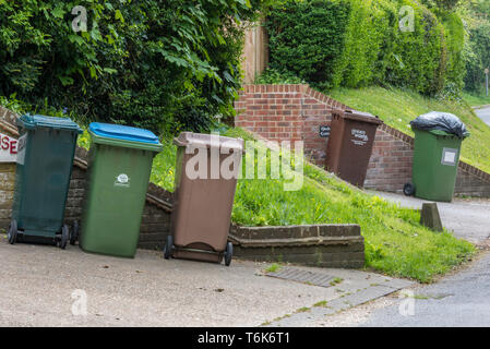 yellow and green plastic wheelie bins awaiting rubbish collection from bin men in a country lane. - Stock Photo