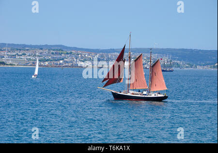 Two masted schooner with red sails in Carrick Roads off Falmouth in Cornwall, England,UK - Stock Photo