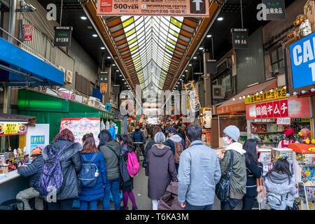 Osaka, Japan - 3 Mar 2018; Japanese local people, tourists and travelers walking and eating at Kuromon Ichiba Market (fish market), Osaka, Japan. - Stock Photo