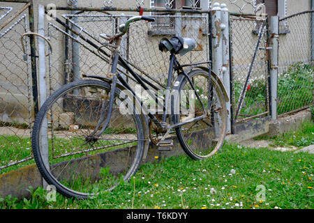 old fashioned bicycle propped against a fence in a rural village zala county hungary - Stock Photo
