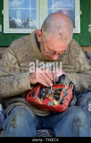 mature man working on a chainsaw to replace the blunt chain with a sharp one zala county hungary - Stock Photo