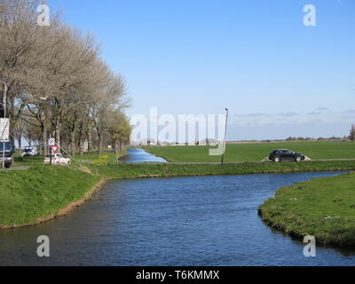 View of the flat landscape and canals as drainage measures in North Holland; a sunny spring day in Edam, North Holland - Stock Photo