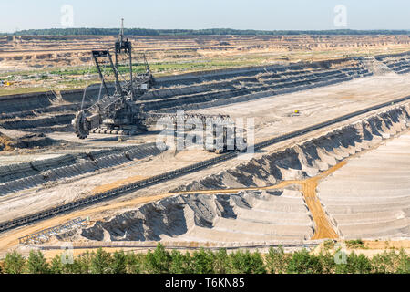 Brown coal open pit landscape with digging excavator in Germany - Stock Photo